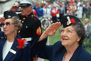 Female veterans saluting flag